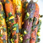 Roasted rainbow carrots with pistachio pesto and a sprinkle of pistachios on a white plate.