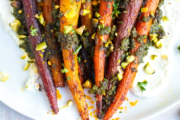 Roasted whole carrots on a white plate with homemade pistachio pesto.