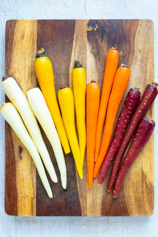 Rainbow carrots that have been peeled and are on a wooden cutting board.