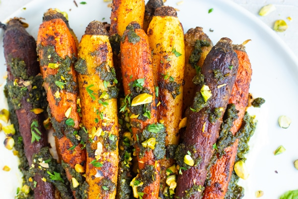 Whole roasted rainbow carrots in a pile on a white plate with pistachios sprinkled around.