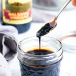 Balsamic glaze being scooped up by a spoon from a clear mason jar container.