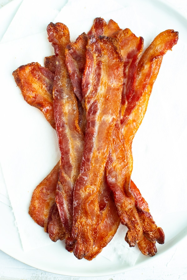 Bacon strips that have been cooked in the oven draining on paper towels.