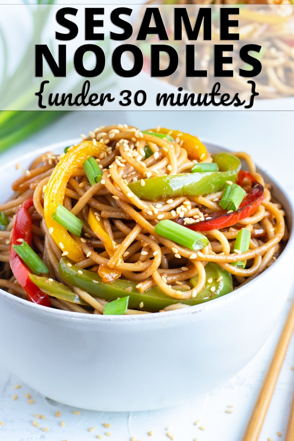 Cold sesame noodles with bell peppers in a white bowl with chopsticks and green onions next to it.