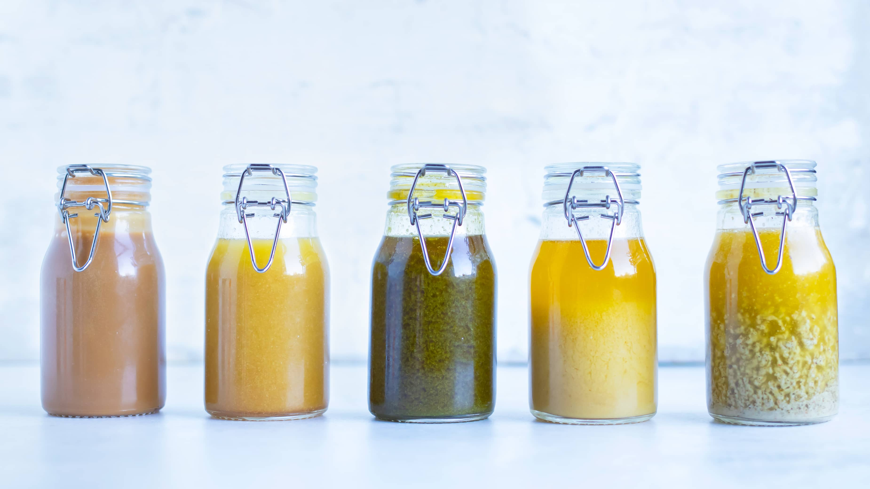 Five glass jars full of healthy homemade salad dressing recipes.