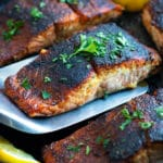 Blackened salmon in a cast iron skillet with lemons and parsley.