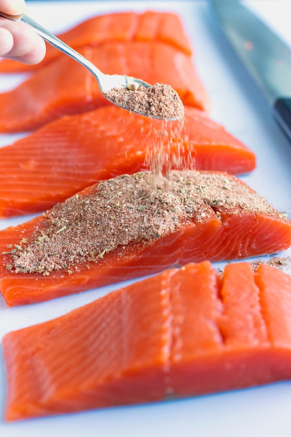 Homemade seasoning mix being sprinkled over salmon to make a blackened salmon recipe.