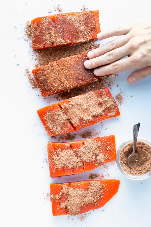 Blackened seasoning mix being rubbed into salmon filets on a white cutting board.