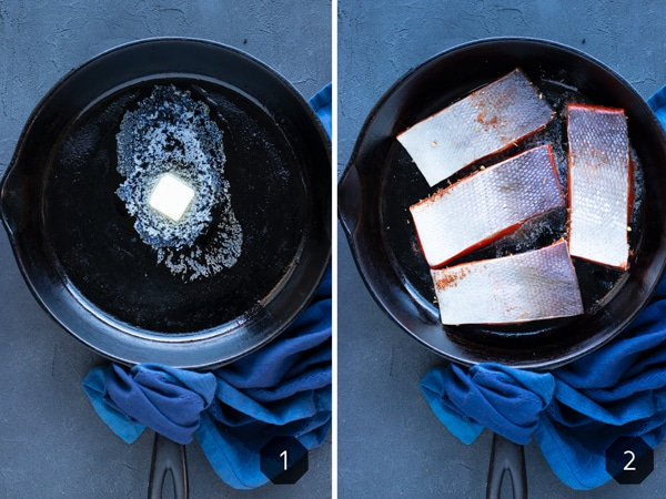 Blackened salmon being cooked in a cast iron skillet with butter.
