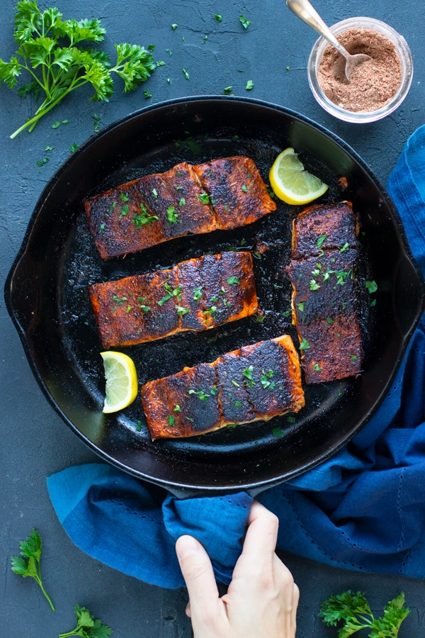 Blackened salmon recipe in a black cast iron skillet with a bowl full of blackened seasoning next to it.