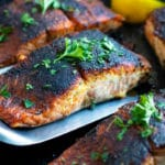 Blackened salmon being picked up by a metal spatula from a skillet.
