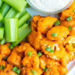 A white plate full of buffalo cauliflower bites, celery sticks, and a bowl full of ranch dressing for a Super Bowl appetizer.