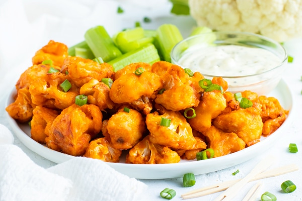 A plate full of baked cauliflower buffalo wings with celery sticks and ranch dressing.