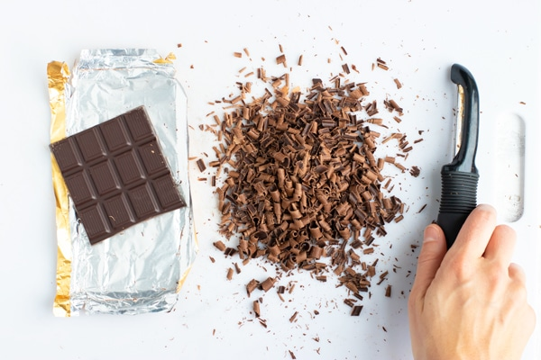 Showing how to make chocolate curls from a chocolate bar with a potato peeler.