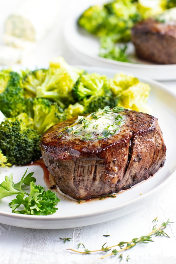 The best filet mignon recipe on a white plate with broccoli.