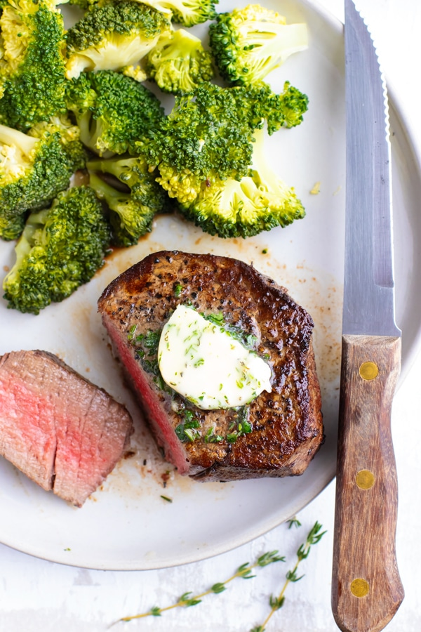 An overhead shot of an oven-baked filet mignon steak with garlic herb butter next to a knife.
