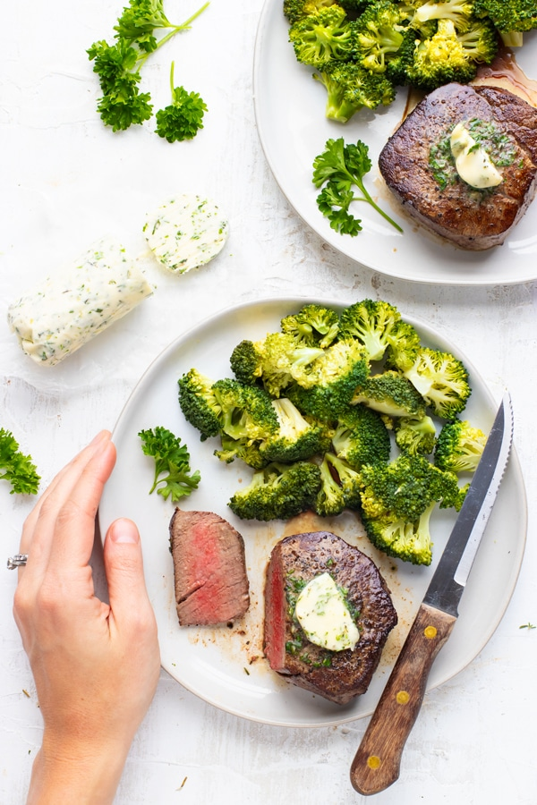 A hand holding a plate with a filet mignon recipe, broccoli, and a knife next to a log of garlic herb butter.