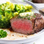 A filet mignon steak that has been cooked to medium-rare on a white plate with a knife and broccoli.