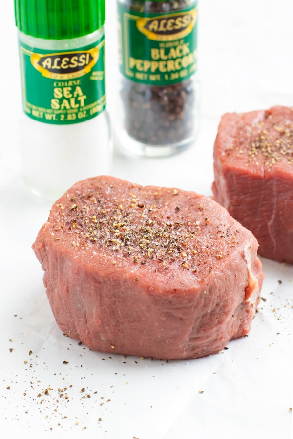 A two-inch thick grass-fed filet mignon steak with a salt and pepper shaker in the back ground.
