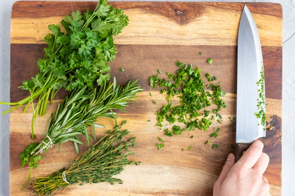 Rosemary, thyme, and parsley on a wooden cutting board with a knife.
