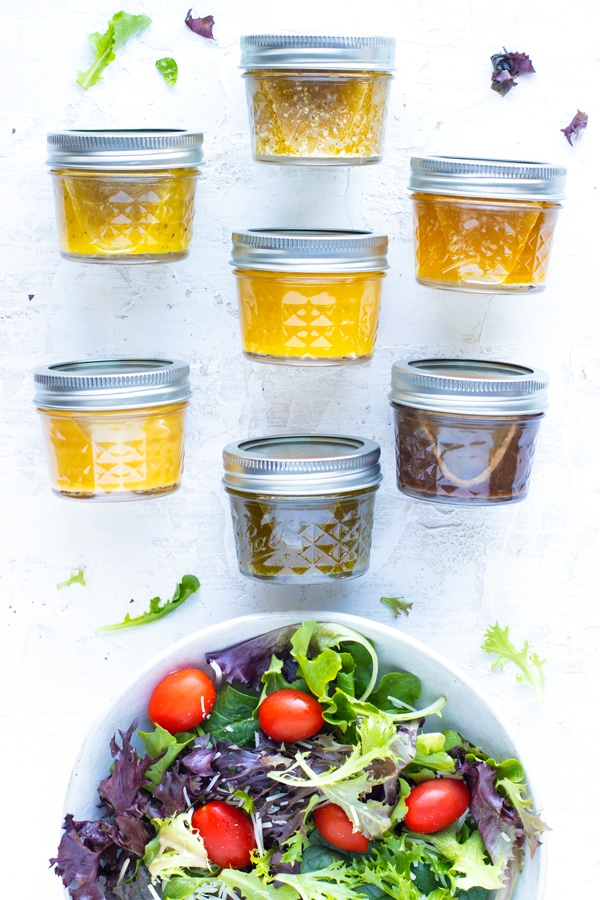 Seven healthy salad dressing recipes in mason jar containers next to a spinach and arugula salad.