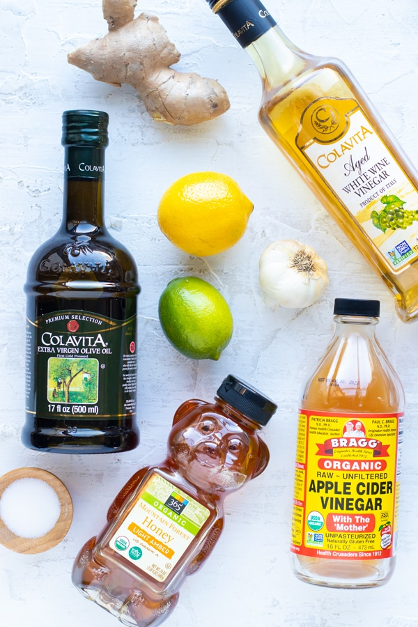 Olive oil, apple cider vinegar, a lime, lemon, garlic clove, and honey on a white table to make healthy salad dressings.