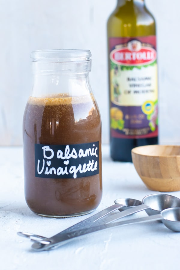Balsamic vinaigrette salad dressing in a clear glass jar with balsamic vinegar in the background.