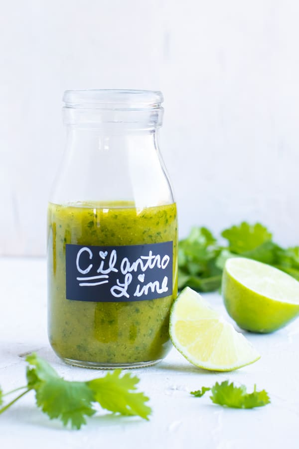 Cilantro lime vinaigrette dressing in a clear glass jar with limes and cilantro next to it.