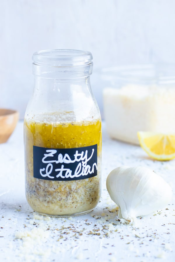Zesty Italian dressing recipe like the kind from Olive Garden next to a head of garlic and Parmesan cheese.