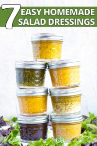 Second mason jars full of homemade salad dressing recipes in a stack with mixed greens around them.