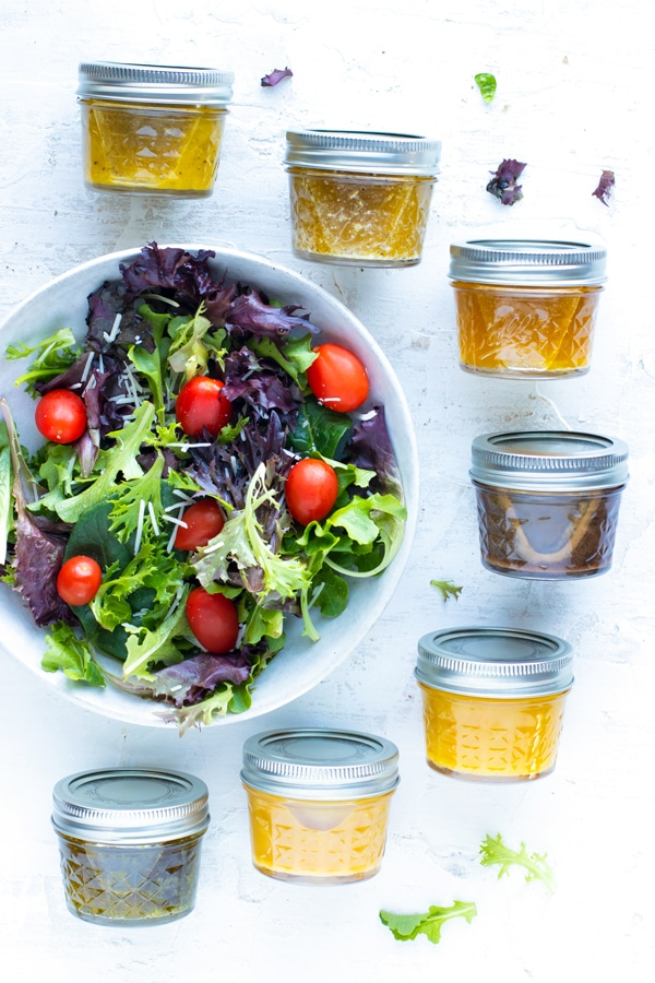Seven homemade and healthy salad dressing recipes in mason jar containers next to a spinach and arugula salad.