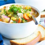 A white bowl full of Instant Pot chicken soup with two pieces of bread and red potatoes next to it.
