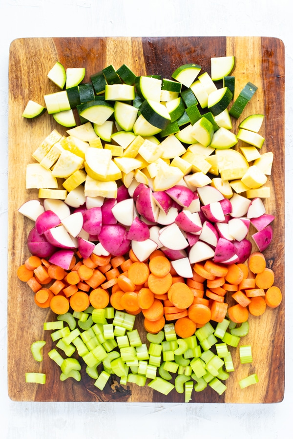 Chopped zucchini, yellow squash, red potatoes, carrots, and celery on a wooden cutting board.