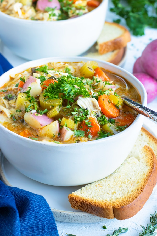A white bowl full of Instant Pot chicken vegetable soup with two pieces of bread and red potatoes next to it.