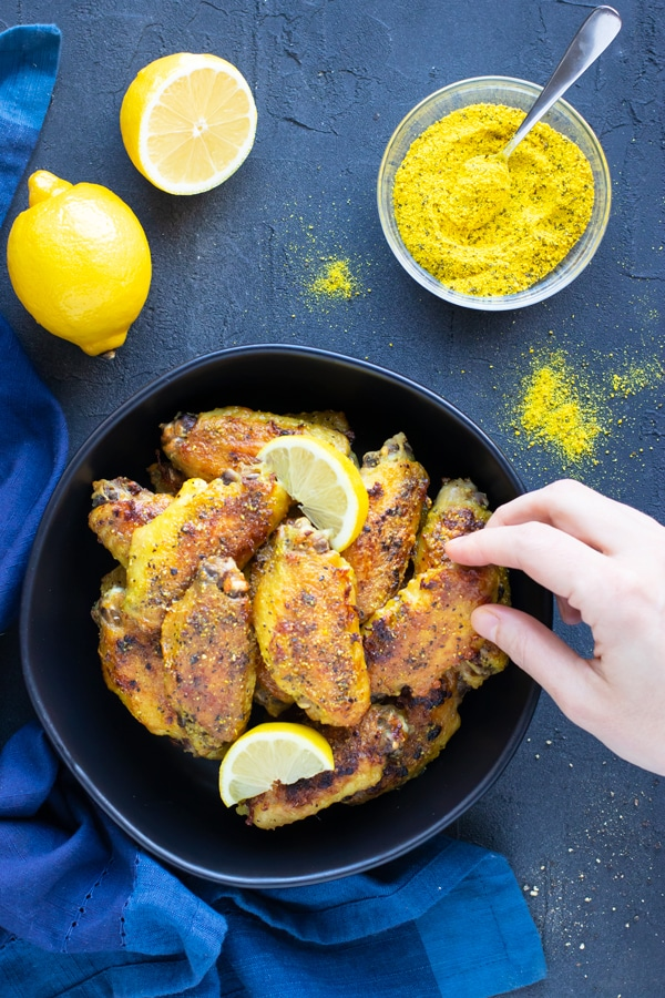 A hand grabbing a lemon pepper chicken wing from a black bowl next to lemon pepper seasoning.