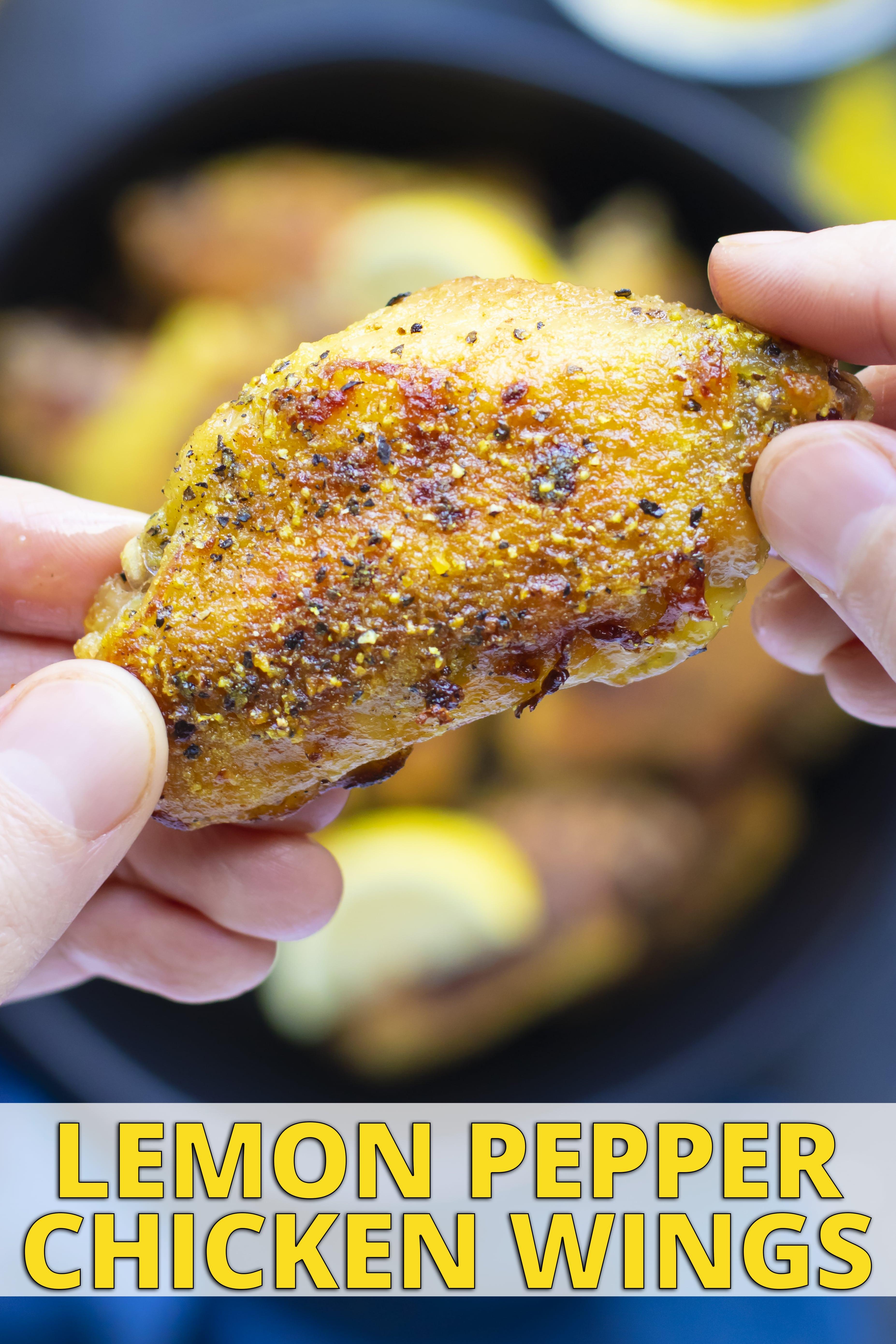 Hands picking up a lemon pepper chicken wing from a bowl of lemon pepper wings.