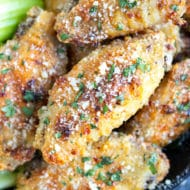 Garlic parmesan chicken wings with a sprinkle of parsley for a Super Bowl party appetizer.
