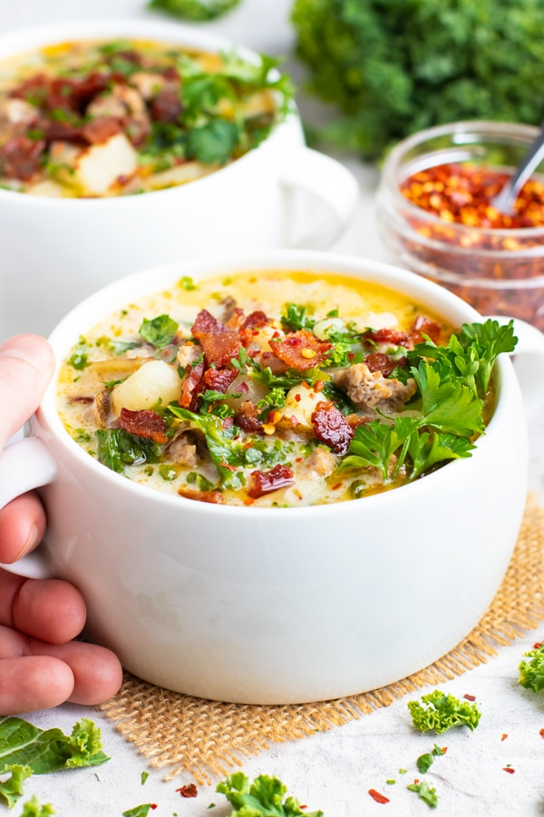 A copycat recipe for Olive Garden zuppa toscana soup in a white bowl with a hand holding it.