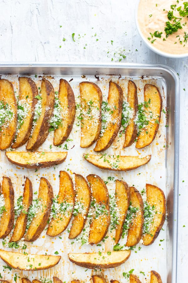 A large baking sheet full of a baked potato wedges recipe with Parmesan cheese and parsley on top.