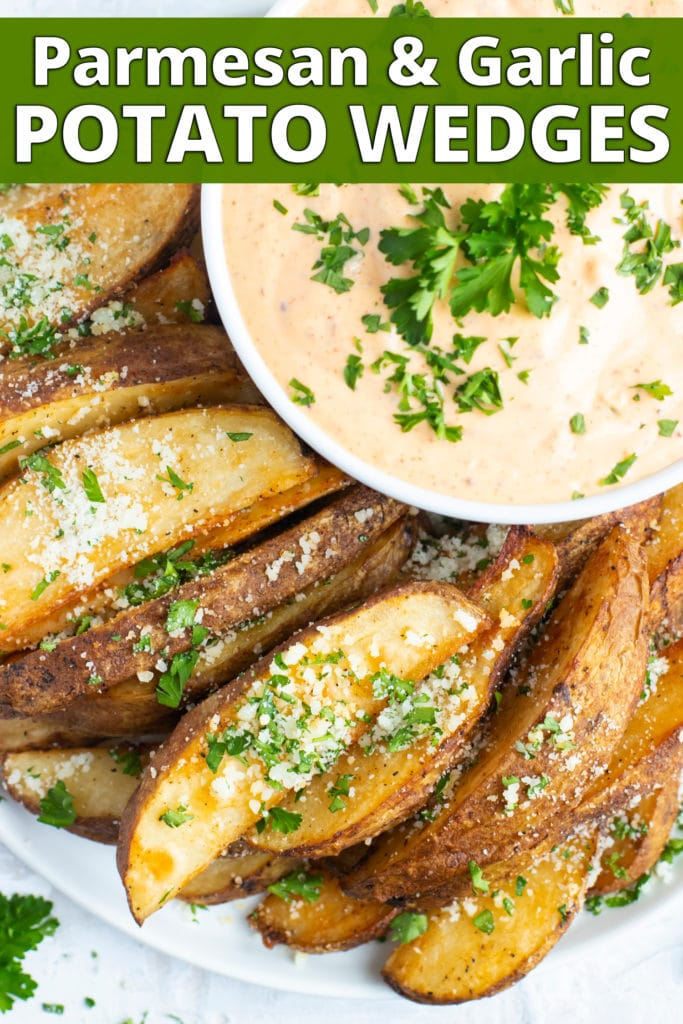A stack of baked potato wedges with Parmesan and parsley sprinkled on top.