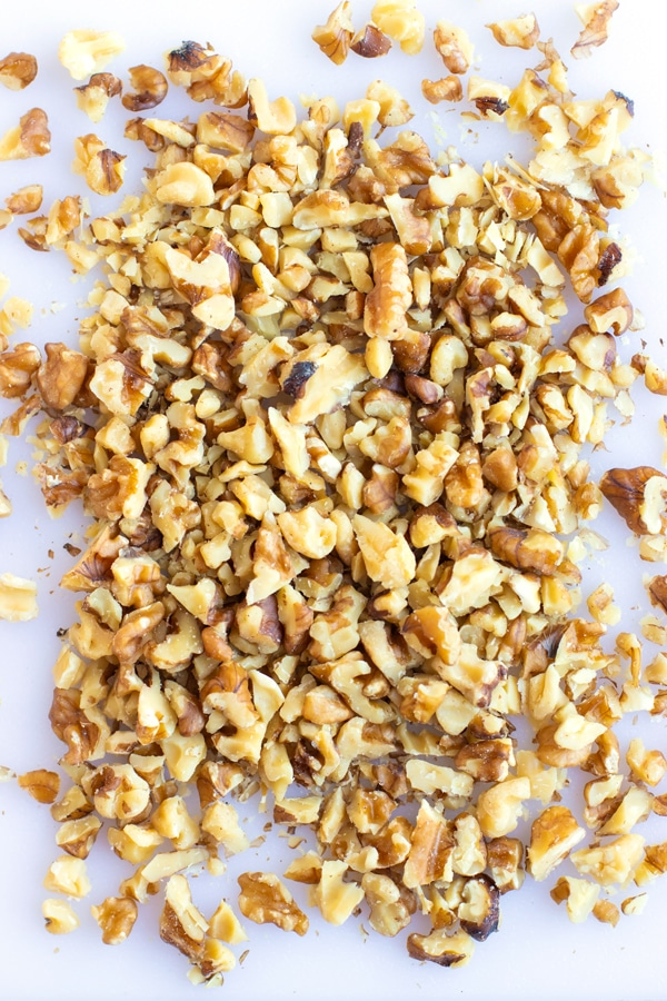 A white cutting board with coarsely chopped walnuts to go into the best banana nut muffins recipe.