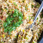 One of the best cauliflower rice recipes that is low-carb and keto in a black bowl with a spoon.