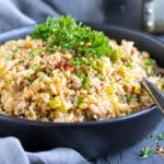 A large serving bowl with a spoon full of cauliflower dirty rice recipe.