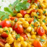 A close-up of vegetarian chickpea curry and tomatoes with basmati rice.