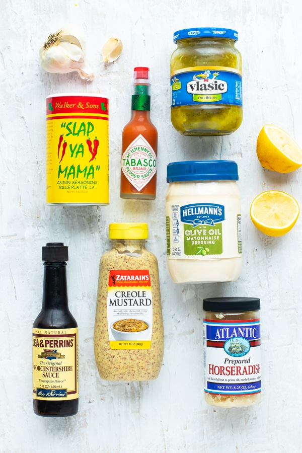 The ingredients for a Cajun remoulade sauce including mayonnaise, mustard, lemon juice, paprika, Cajun seasoning, and horseradish.