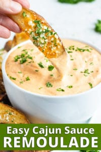 A baked potato wedge being dipped into a bowl full of Cajun remoulade sauce.
