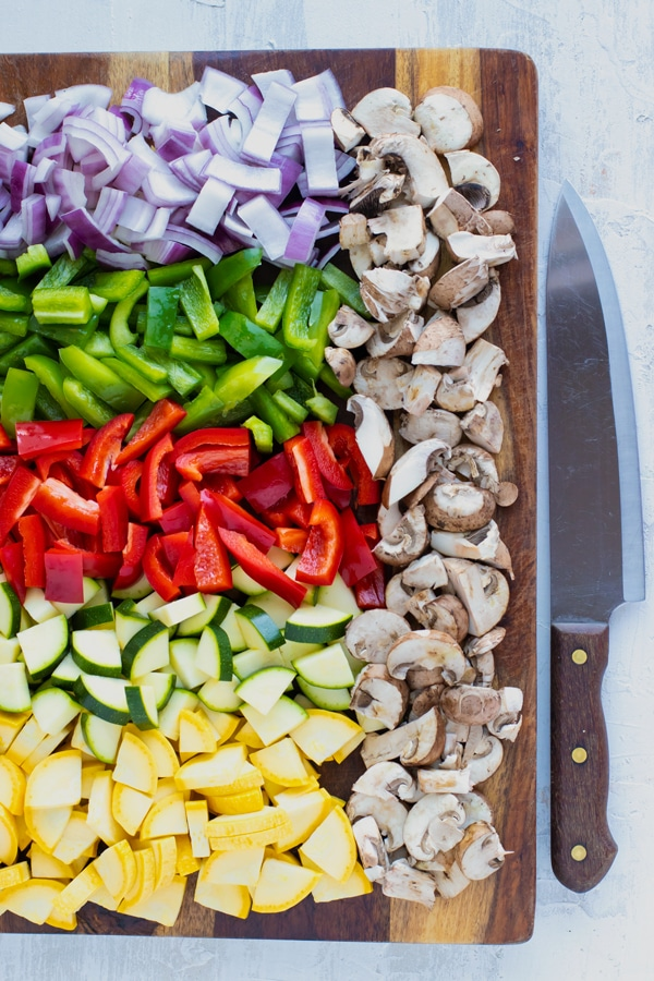 A cutting board full of yellow squash, zucchini squash, red onion, green and red bell pepper, and mushrooms.