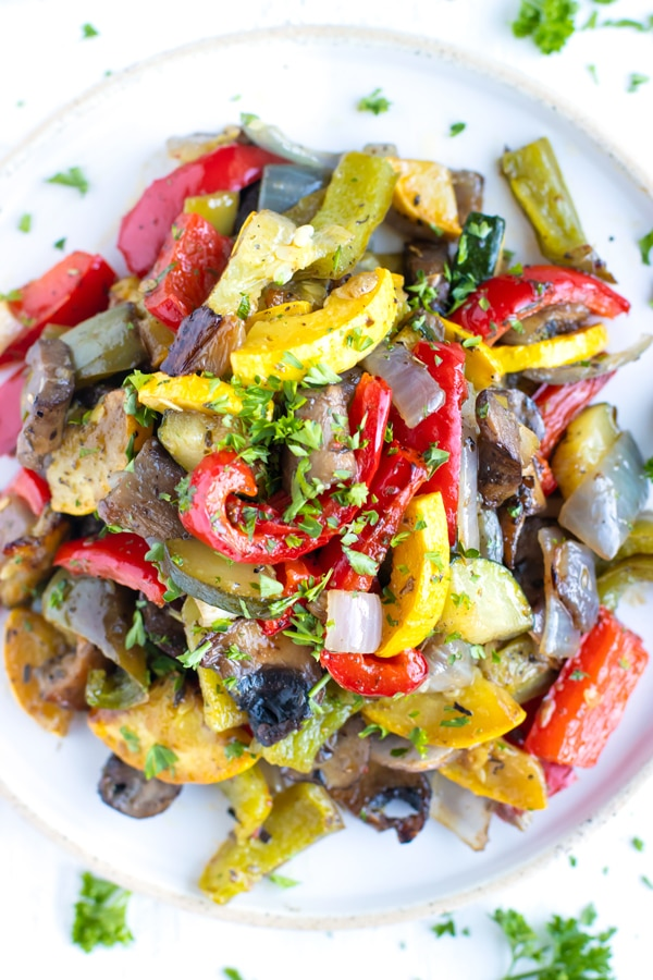 Roasted vegetables on a white plate with parsley sprinkled on top.
