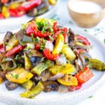 A pile of oven-roasted vegetables on a white plate with another serving in the background.