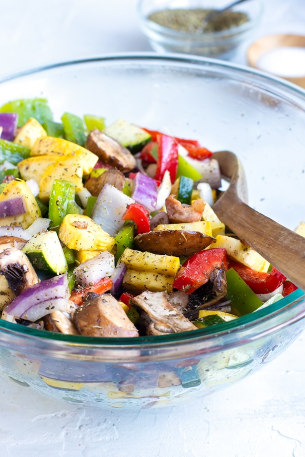 A glass bowl full of chopped zucchini, squash, bell peppers, onions, and mushrooms for a roasted vegetables recipe.