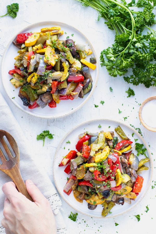 Two white plates full of Italian roasted vegetable medley next to a wooden spoon.